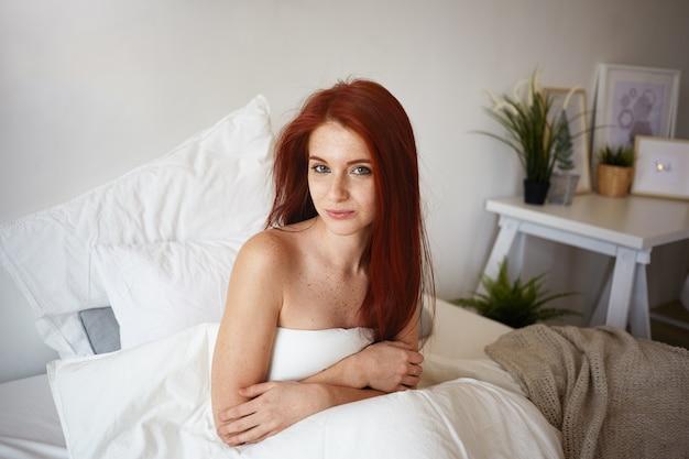Portret van betoverende volwassen europese vrouw met gember lang haar zittend op bed in haar kamer, gewikkeld in een witte deken, glimlachend vreugdevol. rust, ontspanning, bedtijd en beddengoed concept Gratis Foto