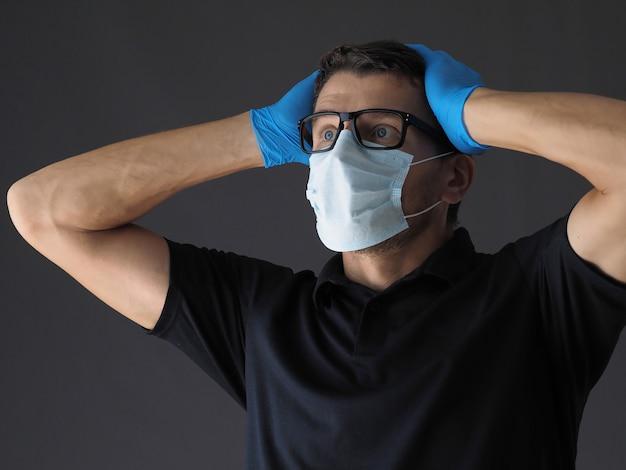 Portret van bezorgd persoon met chirurgische gezichtsmasker virusbescherming en handschoenen houden zijn hoofd in shock en paniek. Premium Foto