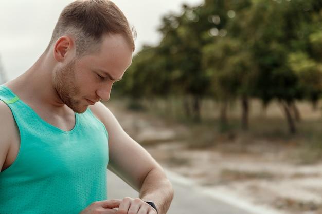 Portret van blanke man in azuurblauwe t-shirt kijken naar fitness tracker lezingen Premium Foto
