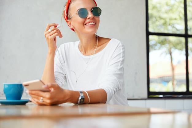 Portret van blij vrouwelijk model oortelefoons zet, geniet van perfecte lied of favoriete muziek, aangesloten op moderne mobiele telefoon, zit aan tafel met kopje koffie tegen café interieur. mensen en rust concept Gratis Foto