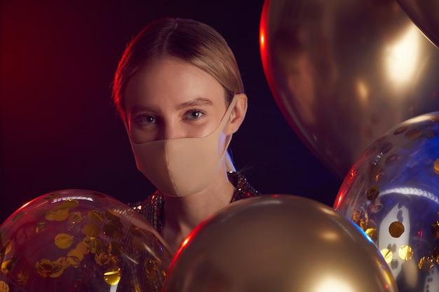 Portret van blonde jonge vrouw die gezichtsmasker draagt en ballons houdt terwijl u geniet van partij in nachtclub, exemplaarruimte dichten Premium Foto