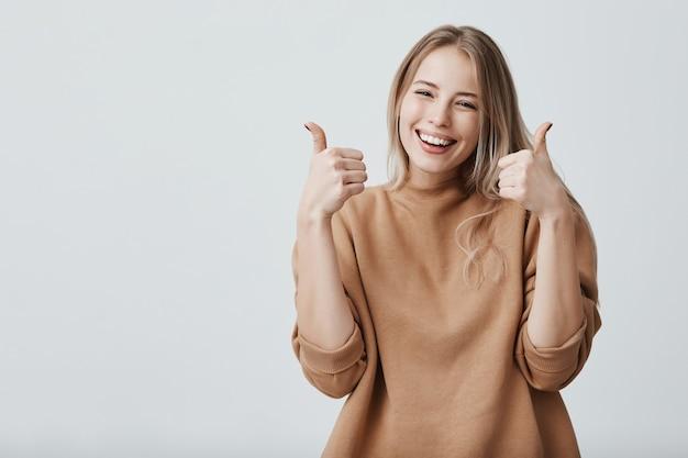 Portret van blonde mooie vrouwelijke vrouw met brede glimlach en omhoog duimen Gratis Foto