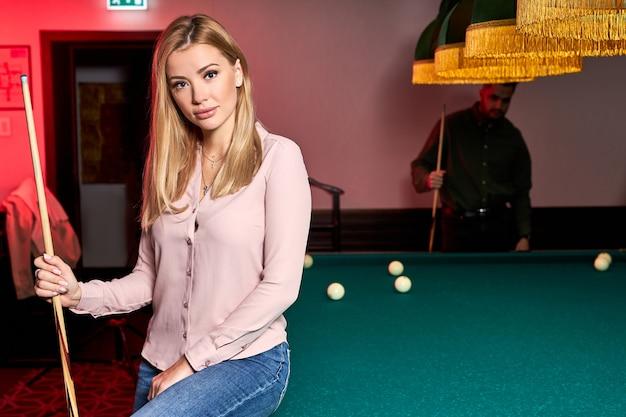 Portret van blonde vrouw zittend op de biljarttafel poseren, het dragen van casual outfit, in de bar, aangename tijd, vakantie doorbrengen Premium Foto