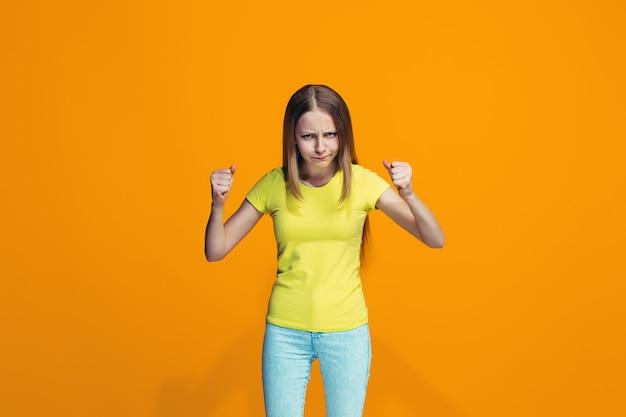 Portret van boos tienermeisje op een oranje muur Gratis Foto