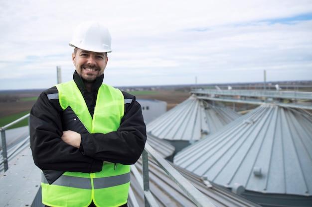 Portret van bouwvakker die zich op daken van hoge silo'sopslagtanks bevindt Gratis Foto