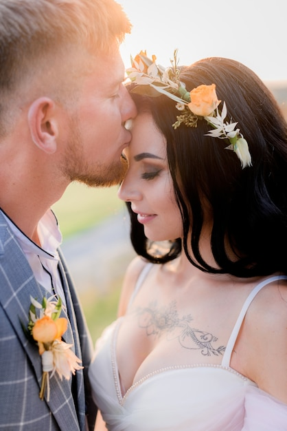 Portret van bruidegom die getatoeëerde bruid kust met open decollete en tedere krans gemaakt van verse bloemen Gratis Foto