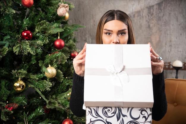 Portret van charismatische vrouw zitten en het openen van een kerstcadeau. hoge kwaliteit foto Gratis Foto