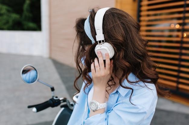 Portret van charmant meisje met glanzend krullend donkerbruin haar, genietend van favoriete muziek in grote witte koptelefoon op bromfiets Gratis Foto