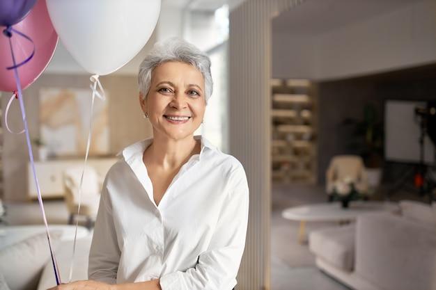 Portret van charmante gelukkig volwassen vrouw draagt formele shirt met plezier op haar pensioen feestje, poseren in kantoor interieur met helium ballonnen Gratis Foto