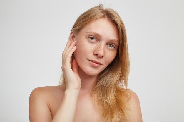 Portret van charmante groenogige jonge roodharige vrouw die zachtjes haar wang aanraakt met opgeheven hand en positief kijkt, staande over een witte muur Gratis Foto