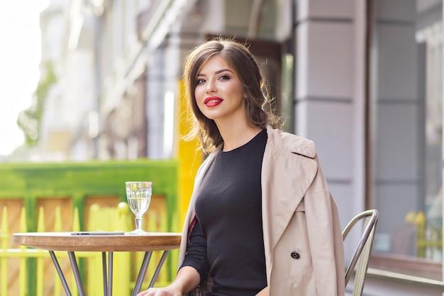 Portret van charmante mooie vrouw close-up met rode lippen dragen zwarte jurk en beige jas rusten in zomer cafetaria met een glas water Gratis Foto