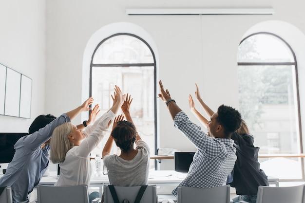 Portret van de achterkant van vermoeide studenten die zich uitstrekken na lang werk. indoor foto van kantoorpersoneel gek rond tijdens bijeenkomst in conferentiezaal met grote ramen. Gratis Foto