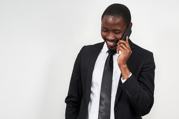 Portret van de afrikaanse mens die terwijl het spreken op de telefoon met grijze muur glimlacht Premium Foto