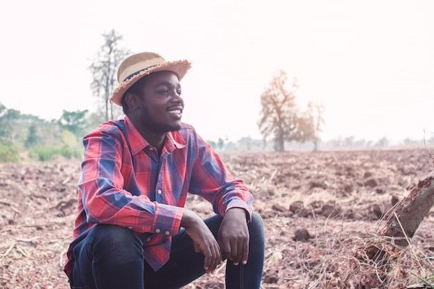Portret van de afrikaanse zitting van de landbouwersmens bij het gebied Premium Foto