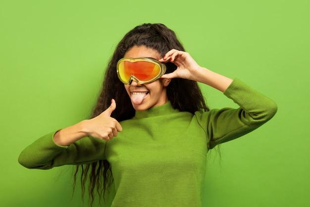 Portret van de afro-amerikaanse jonge brunette vrouw in skimasker op groen Gratis Foto