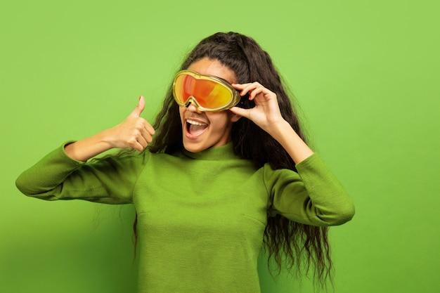 Portret van de afro-amerikaanse jonge brunette vrouw in skimasker op groene studio achtergrond. concept van menselijke emoties, gezichtsuitdrukking, verkoop, advertentie, wintersport en vakanties. glimlachend, duim omhoog. Gratis Foto