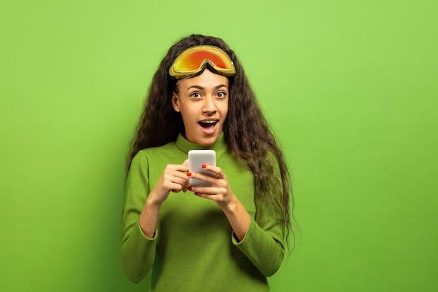 Portret van de afro-amerikaanse jonge brunette vrouw in skimasker op groene studio achtergrond. concept van menselijke emoties, gezichtsuitdrukking, verkoop, advertentie, wintersport en vakanties. met behulp van smartphone. Gratis Foto