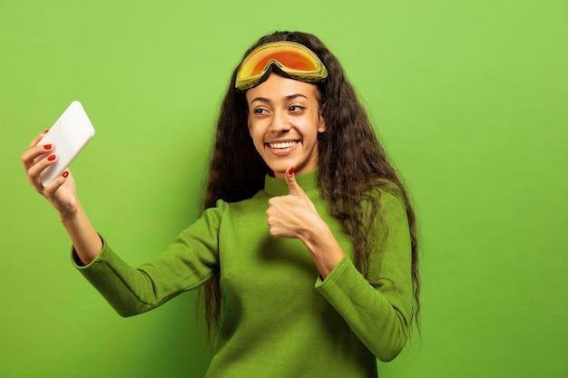 Portret van de afro-amerikaanse jonge brunette vrouw in skimasker op groene studio achtergrond. concept van menselijke emoties, gezichtsuitdrukking, verkoop, advertentie, wintersport en vakanties. selfie of vlog maken. Gratis Foto