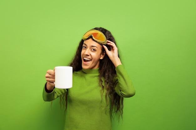 Portret van de afro-amerikaanse jonge brunette vrouw in skimasker op groene studio achtergrond. concept van menselijke emoties, gezichtsuitdrukking, verkoop, advertentie, wintersport en vakanties. thee of koffie drinken. Gratis Foto