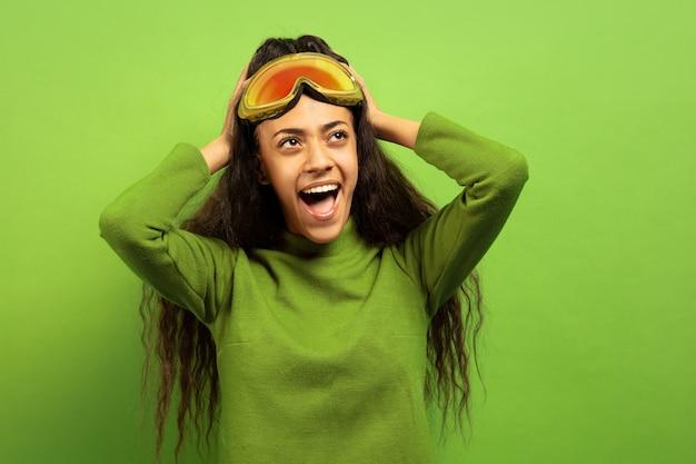 Portret van de afro-amerikaanse jonge brunette vrouw in skimasker op groene studio achtergrond. concept van menselijke emoties, gezichtsuitdrukking, verkoop, advertentie, wintersport en vakanties. verbaasd geschreeuw. Gratis Foto