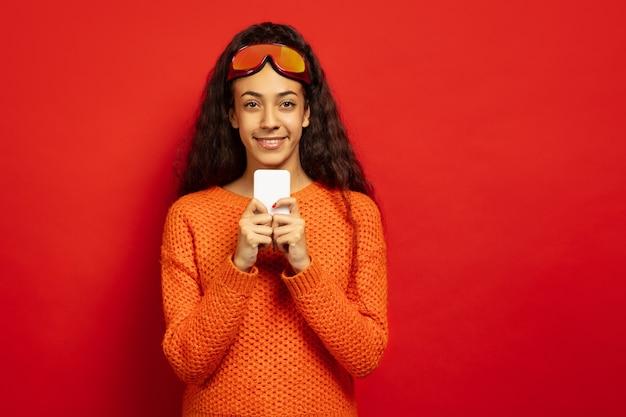 Portret van de afro-amerikaanse jonge brunette vrouw in skimasker op rode studio achtergrond. concept van menselijke emoties, gezichtsuitdrukking, verkoop, advertentie, wintersport en vakanties. chatten met telefoon. Gratis Foto