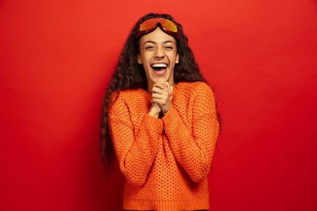 Portret van de afro-amerikaanse jonge brunette vrouw in skimasker op rood Gratis Foto