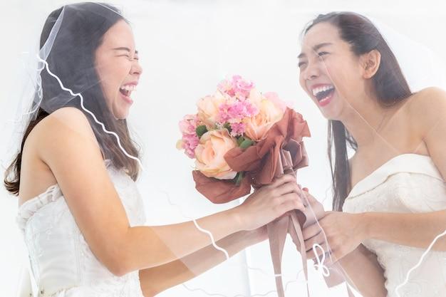 Portret van de aziatische homoseksuele bloem van de paarholding in bruidkleding. concept lgbt-lesbienne. Premium Foto