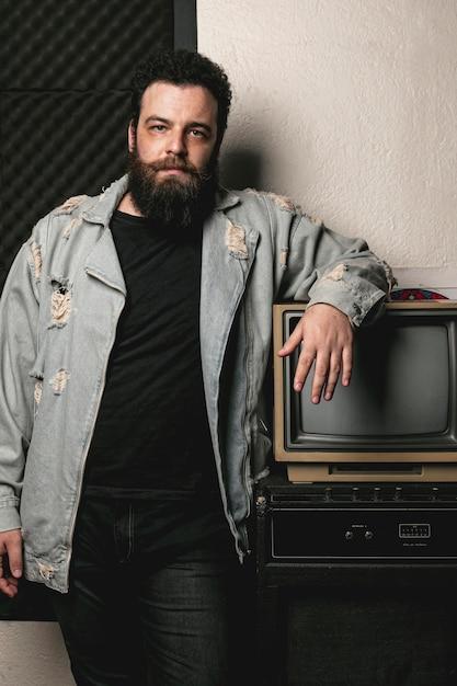 Portret van de baardmens naast uitstekende tv Gratis Foto