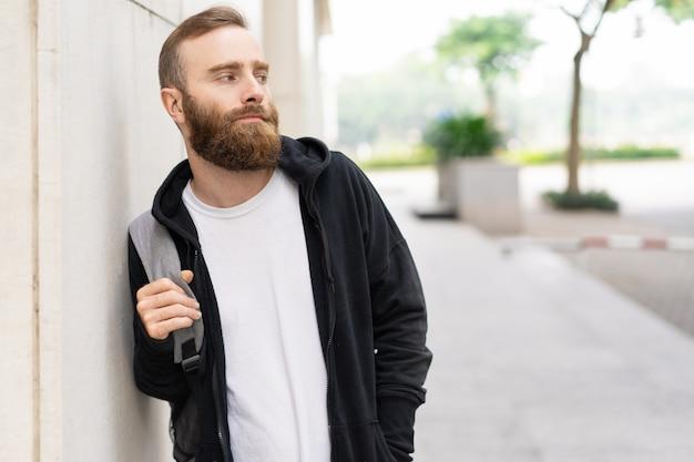 Portret van de ernstige jonge, bebaarde man met rugzak buitenshuis Gratis Foto