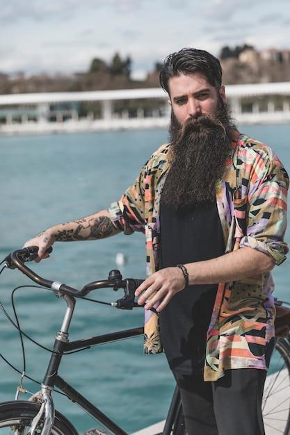 Portret van de gebaarde jonge mens die zich met zijn fiets bevindt die camera bekijkt Gratis Foto