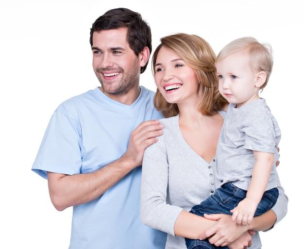 Portret van de gelukkige familie die met klein kind zijwaarts kijkt - geïsoleerd Gratis Foto