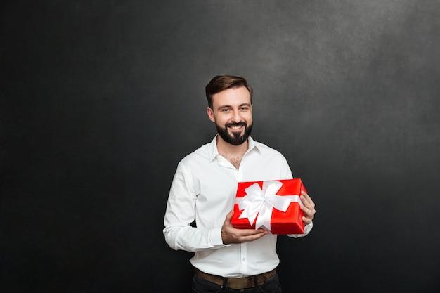 Portret van de gelukkige gebaarde mens die rode giftdoos houden en de camera over donkergrijze muur bekijken Gratis Foto