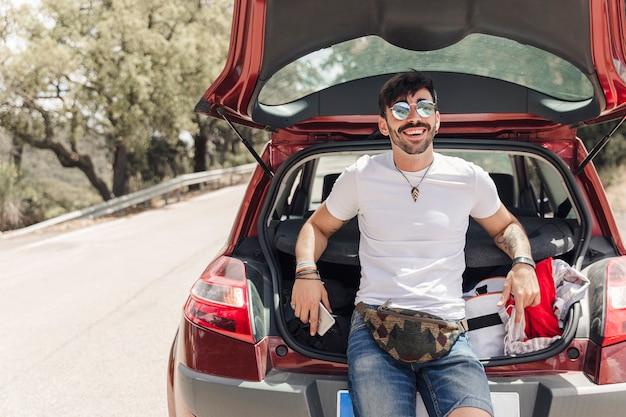 Portret van de gelukkige jonge mens die zich dichtbij de auto op weg bevindt Gratis Foto