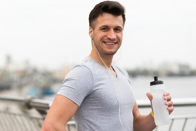 Portret van de gelukkige mannelijke fles van het holdingswater Gratis Foto