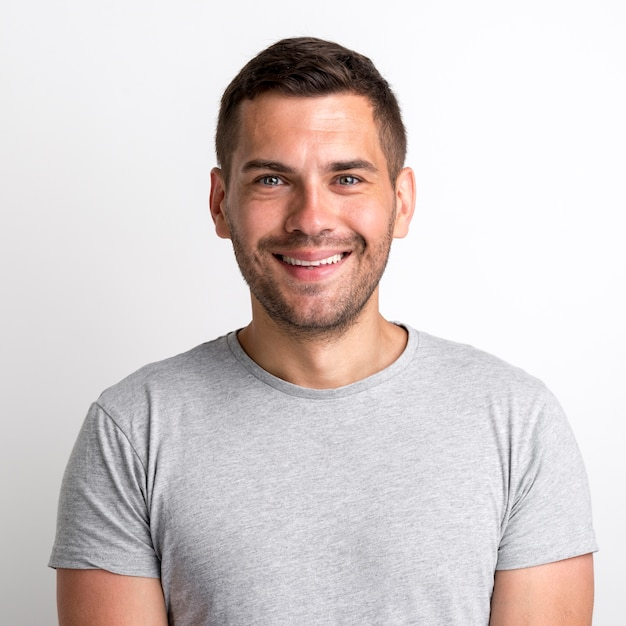 Portret van de glimlachende charmante jonge mens in grijze t-shirt die zich tegen duidelijke achtergrond bevinden Gratis Foto
