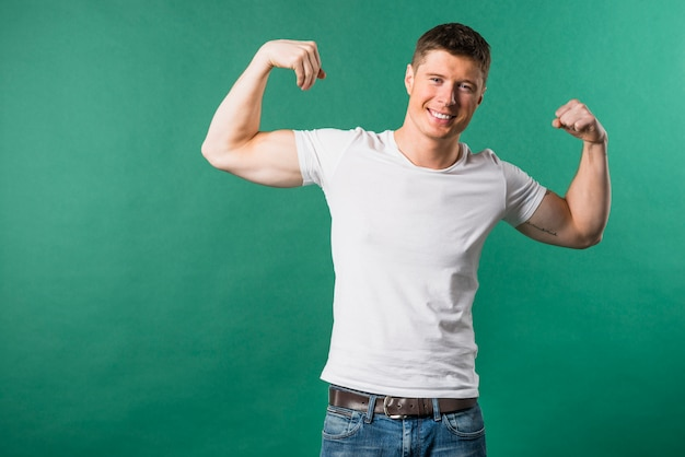 Portret van de glimlachende jonge mens die zijn spier buigt tegen groene achtergrond Gratis Foto