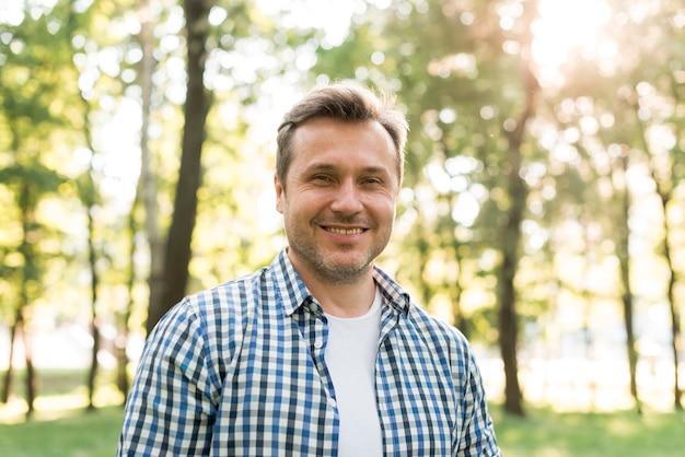Portret van de glimlachende mens die zich in park bevindt Gratis Foto