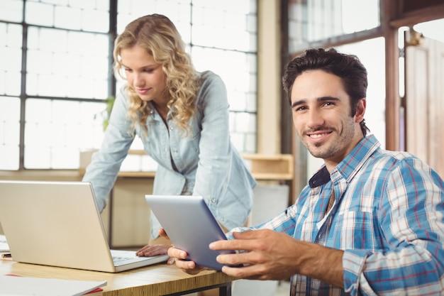 Portret van de glimlachende tablet van de mensenholding met vrouw die in bureau werken Premium Foto