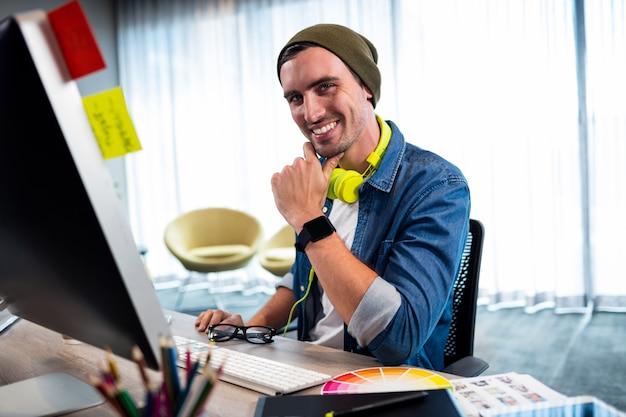 Portret van de glimlachende toevallige mens die bij computerbureau werkt Premium Foto