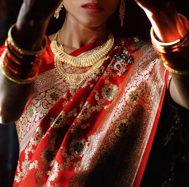 Portret van de hindoe-bruid in traditionele rode sari met gouden acce Gratis Foto