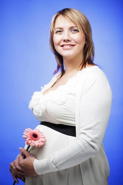 Portret van de jonge gelukkige glimlachende zwangere vrouw met bloem Premium Foto