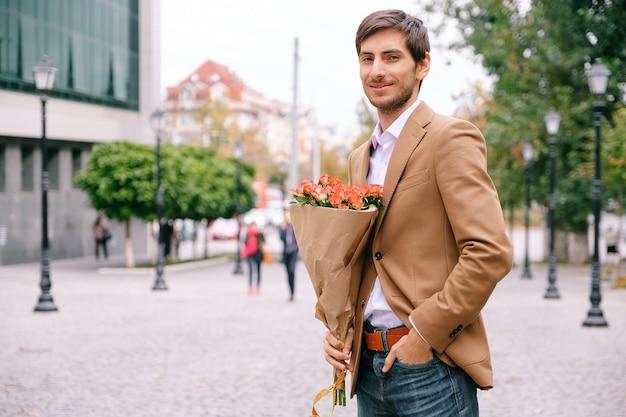Portret van de jonge knappe man die lacht houden van een bos rozen Gratis Foto
