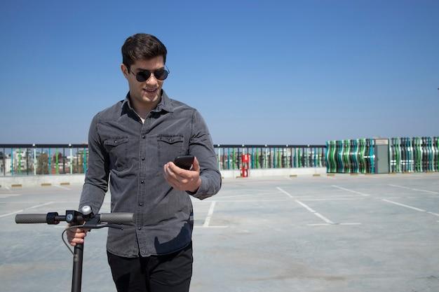 Portret van de jonge knappe man die op zijn elektrische autoped staat en zijn slimme telefoon bekijkt Gratis Foto