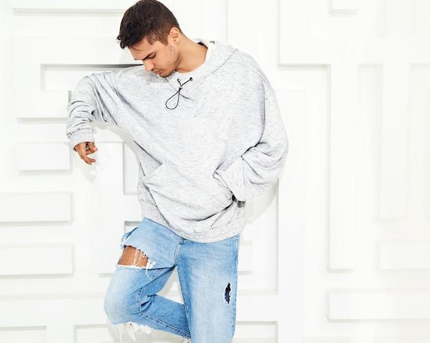 Portret van de jonge knappe modelmens gekleed in grijze toevallige hoodiekleren die dichtbij geweven witte muur stellen Gratis Foto