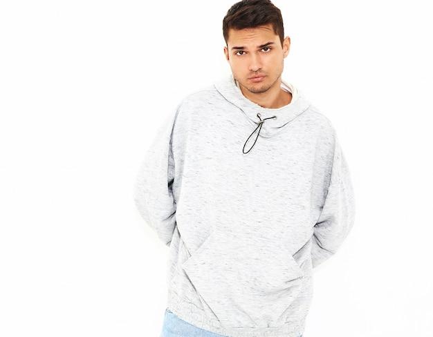 Portret van de jonge knappe modelmens gekleed in grijze toevallige hoodiekleren die op witte muur stellen. geïsoleerd Gratis Foto