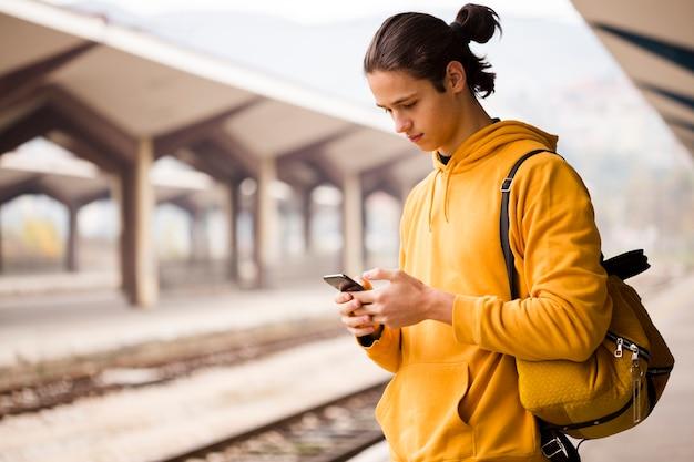 Portret van de jonge mens die zijn telefoon controleert Gratis Foto