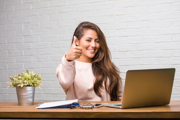 Portret van de jonge zitting van de studenten latijnse vrouw op haar vrolijk en opgewekt bureau Premium Foto