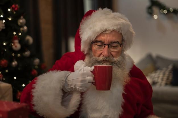 Portret van de kerstman die een kerstmisdrank heeft Gratis Foto