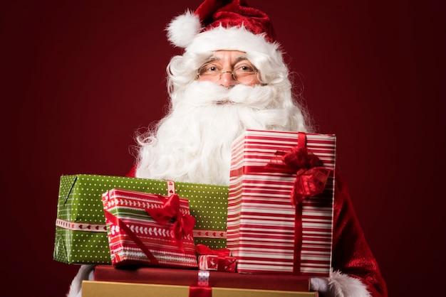 Portret van de kerstman met geschenkdozen op rode achtergrond Gratis Foto