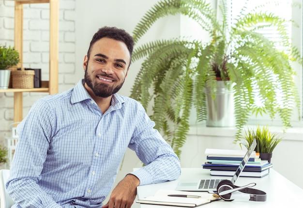 Portret van de knappe afrikaanse zwarte jonge bedrijfsmens die aan laptop op kantoor werken Premium Foto